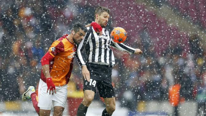 BACK ON: Llorente of Juventus challenges Zan of Galatasaray during their Champions League match in Istanbul which resumed on Wednesday at 1pm.