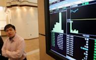 A man watches trading activity of IHH Healthcare Global shares on an electronic display shortly after the company's listing debut at Malaysia Stock Exchange in Kuala Lumpur on July 25, 2012. Fast-growing IHH employs 24,000 people in 30 hospitals and clinics in Malaysia, Singapore, Turkey, China and other Asian markets