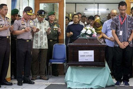 Police officers and family members of Hayati Lutfiah, a passenger of AirAsia QZ8501, pray next to her coffin at Bhayankara Hospital in Surabaya January 1, 2015. REUTERS/Athit Perawongmetha