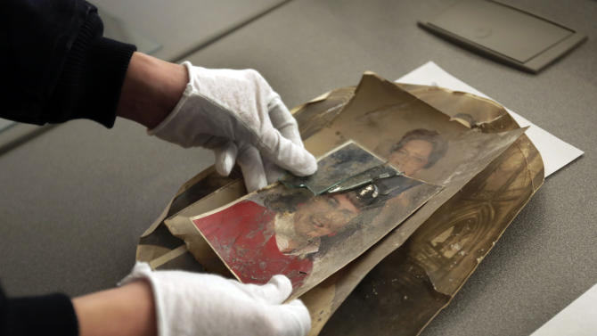 In this Saturday, Feb. 2, 2013 photo, damaged photos belonging to Florence Catania, of Deer Park, N.Y., are evaluated during restoration by Operation Photo Rescue-Hurricane Sandy, at New York's School of Visual Arts. Of all the pictures of Superstorm Sandy's destruction, some of the most lingering are the warped, stained ones that sat on the walls and shelves of flooded homes. The Sandy project promises to be one of Operation Photo Rescue's most expert and ambitious efforts yet. (AP Photo/Richard Drew)