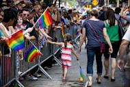 A girl hi-fives a reveler as she marches in the New York City Gay Pride on June 24, 2012. The annual civil rights demonstration commemorates the Stonewall riots of 1969, which erupted after a police raid on a gay bar, the Stonewall Inn on Christopher Street