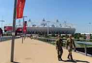 Soldiers walk to their post at the Olympic Stadium in London. Britain drafted another 1,200 troops Tuesday to plug a security gap at the London Olympics left by the failure of a private security firm to provide enough guards