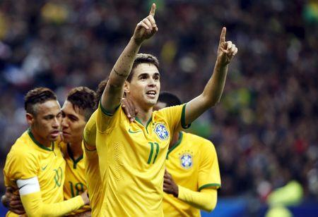 Brazil's Oscar celebrates with team mates after scoring against France during their international friendly soccer match against France at the Stade de France, in Saint-Denis