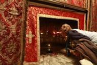 A woman prays inside the Grotto in the Church of the Nativity, traditionally believed to be the birthplace of Jesus, as preparations for Christmas celebrations get underway in the West Bank biblical town of Bethlehem on December 23, 2012.