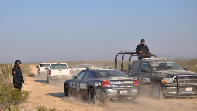 State and federal police drive along a dirt road leading to a ranch near the town of Mina, in northern Mexico, Monday, Jan. 28, 2013. At least eight bodies were found in a well near this ranch on Sunday near the site where 20 people went missing late last week, including members of a Colombian-style band, according to a state forensic official. Officials could not confirm whether the bodies belonged to 16 members of the band Kombo Kolombia and their crew, who were reported missing late last week after playing a private show in a bar in the neighboring town of Hidalgo, north of Monterrey. (AP Photo/Emilio Vazaquez)