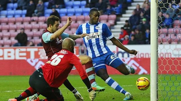 Burnley's Danny Ings is beaten to the ball by Wigan's Leon Barnett