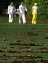 Rickie Fowler walks past debris on the fairway after a overnight storm as play was delayed during a practice round prior to the start of the Masters at Augusta National Golf Club on April 4, 2012 in Augusta, Georgia. Groundstaff scurried to clean up the debris on Wednesday morning as players completed their preparations