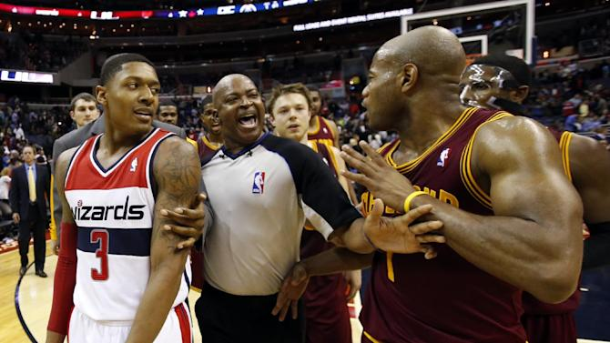 Washington Wizards guard Bradley Beal (3) and Cleveland Cavaliers guard Jarrett Jack (1) are separated by a referee after an NBA basketball game on Saturday, Nov. 16, 2013, in Washington. The Cavaliers won 103-96 in overtime
