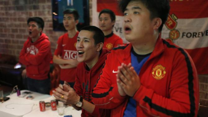 Fans of Manchester United Shanghai fan club react at a bar in Shanghai