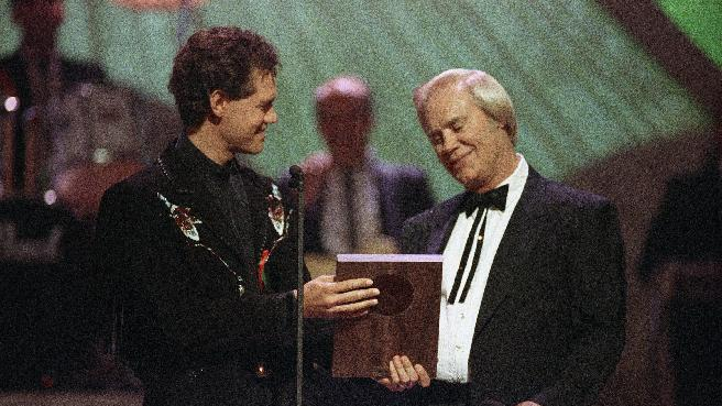 "FILE - In this Sept. 30, 1992 file photo, Country music legend George Jones accepts his Country Music Hall of Fame award from Randy Travis, left, during the Country Music Association Awards show, Nashville, Tenn. Jones, the peerless, hard-living country singer who recorded dozens of hits about good times and regrets and peaked with the heartbreaking classic ""He Stopped Loving Her Today,"" has died. He was 81. Jones died Friday, April 26, 2013 at Vanderbilt University Medical Center in Nashville after being hospitalized with fever and irregular blood pressure, according to his publicist Kirt Webster. (AP Photo/Mark Humphrey, file)"