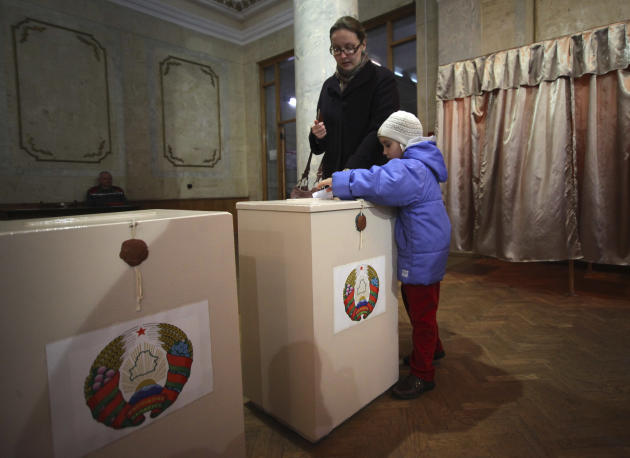 A Belarusian woman with a child casts her ballot paper at a polling station during parliamentary elections in Minsk, Belarus, Sunday, Sept. 23, 2012. Belarus is holding parliamentary elections Sunday