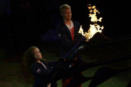 Britain's swimmer Eleanor Simmonds (L) and sprinter Jonnie Peacock colllect the Paralympic flame as the cauldron unwinds for the final time during the closing ceremony of the London 2012 Paralympic Games at the Olympic Stadium in east London.