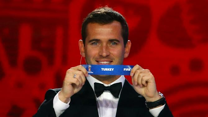 """Former Russian soccer player Kerzhakov holds up the slip showing """"Turkey"""" during the preliminary draw for the 2018 FIFA World Cup at Konstantin Palace in St. Petersburg"""