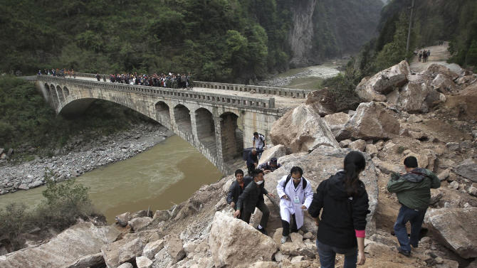 People walk on rocks fallen due to a landslide triggered by a strong quake in Baosheng township of Lushan county in southwest China's Sichuan province Sunday, April 21, 2013. Saturday's earthquake in Sichuan province killed over 200 people, China's Xinhua News Agency said. (AP Photo) CHINA OUT