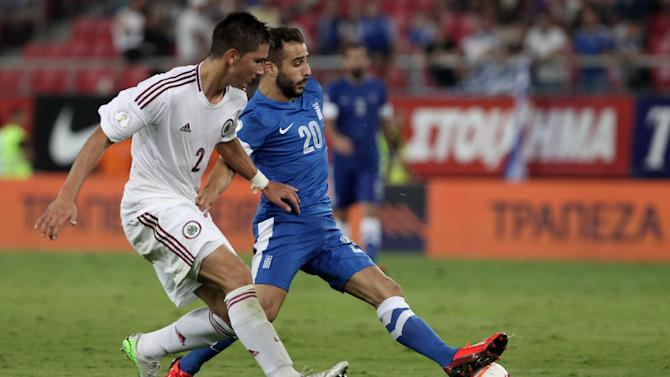 Greece's Giannis Fetfatzidis, right, and Latvia's Vitalijs Maksimenko challenge for the ball during their World Cup Group G qualifying soccer match at the Karaiskaki stadium in Piraeus port, near Athens, on Tuesday, Sept. 10, 2013
