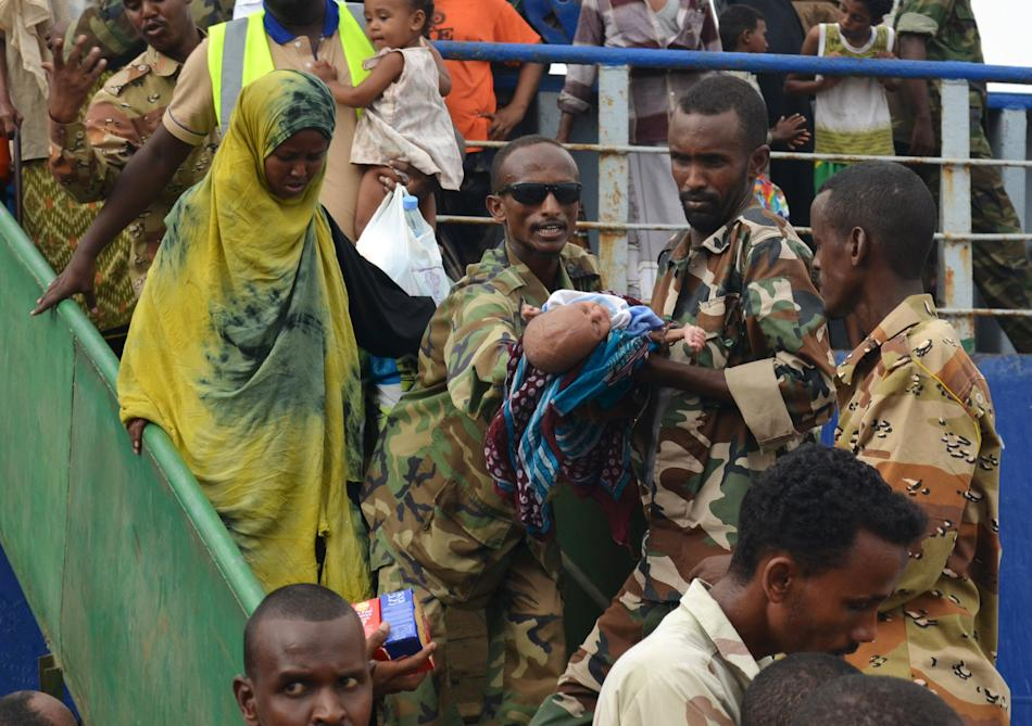 Somalia soldiers help a baby from a ship, with hundreds of families fleeing the ongoing violence in Yemen, arriving at the port of Bosasso in Somalia's Puntland region