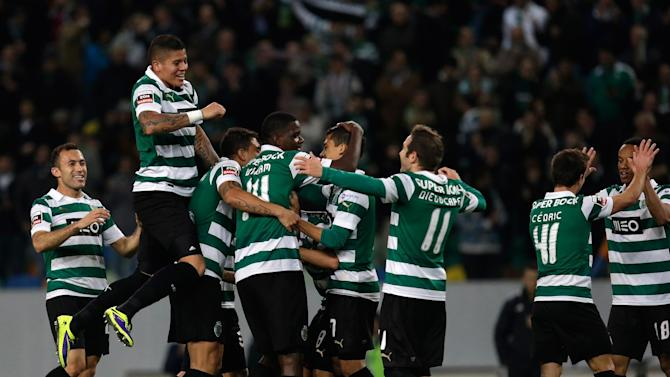 Sporting players celebrate after scoring their second goal during their Portuguese league soccer match against Belenenses Saturday, Dec. 14 2013, at Sporting's Alvalade stadium in Lisbon. Sporting defeated Belenenses 3-0 to remain at the top of the table