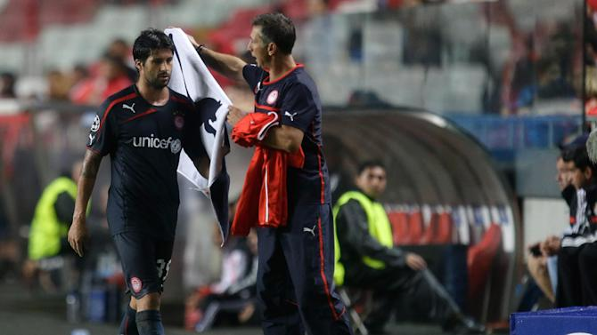 Olympiacos' Alejandro Dominguez, left, walks to the bench after being substituted during the Champions League group C soccer match between SL Benfica and Olympiacos FC in Lisbon, Wednesday, Oct. 23, 2013. Dominguez scored a goal in the game that ended in a 1-1 draw