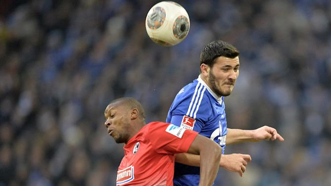 Schalke's Sead Kolasinac, up, and Freiburg's Karim Guede of Slovakia challenge for the ball during the German Bundesliga soccer match between FC Schalke 04 and SC Freiburg in Gelsenkirchen, Germany, Sunday, Dec. 15, 2013