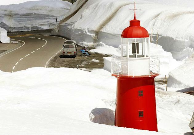Dutch tourists relax in front of a lighthouse on the Central Swiss Oberalp Pass mountain pass, located at 2,046 metres (6,713 ft) above sea level.