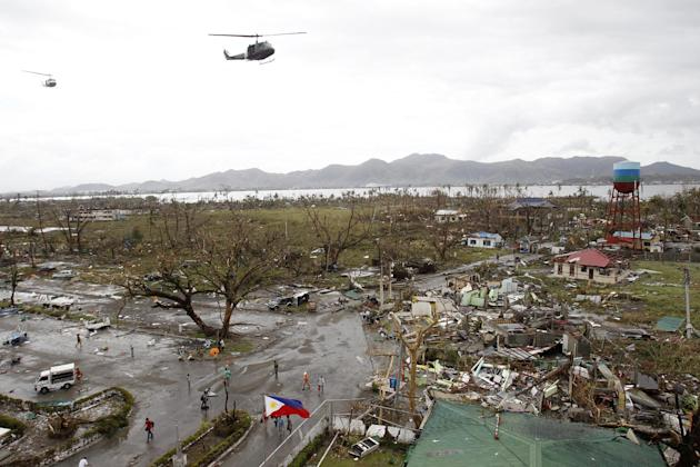 Helicopters hover over the damaged area after super Typhoon Haiyan battered Tacloban city