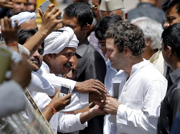 A farmer speaks with India's Congress Party Vice President Rahul Gandhi (R) during a meeting outside Gandhi's residence in New Delhi