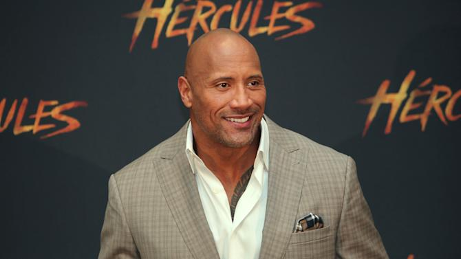 """U.S. actor Dwayne Johnson poses for photos as he arrives for an event to promote his film """"Hercules,"""" in Mexico City, Monday, August 18, 2014. (AP Photo/Marco Ugarte)"""