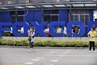 Workers are seen outside the Foxconn factory in Shenzhen, in 2010. Electronics giant Foxconn, whose vast plants in China churn out products for Apple and other tech firms, shut a factory on Monday after a brawl involving some 2,000 workers