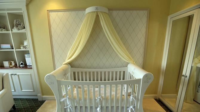 In this Tuesday, April 30, 2013 photo, a cot bed adorned with a coronet and drapes is seen at a hotel nursery suite, designed by Dragons, a small British family business that was also tapped to design nurseries for British royals, at a central London hotel. Britain's Prince William and Kate, formally known as the Duchess of Cambridge, plan to move into apartments at London's Kensington Palace soon after the baby is born in July. Few will ever get a glimpse inside the room where the future British monarch will grow up, but the designers hired by late Princess Diana to create her sons' William and Harry's nursery at the palace can offer some expert hints. (AP Photo/Lefteris Pitarakis)