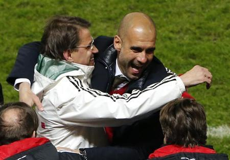 Bayern Munich's coach Pep Guardiola celebrates with an undentified person (L) after the German first division Bundesliga soccer match against Hertha Berlin, in Berlin March 25, 2014. REUTERS/Fabrizio Bensch