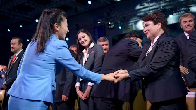 Two-time freestyle skiing Olympic medalist Li Nina of China shakes hands with a delegate from the Kazakh city of Almaty after Beijing was named to host the 2022 Olympic Winter Games over Almaty, at the IOC session in Kuala Lumpur