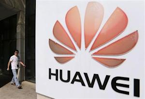 A man walks past a Huawei company logo outside the entrance of a Huawei office in Wuhan