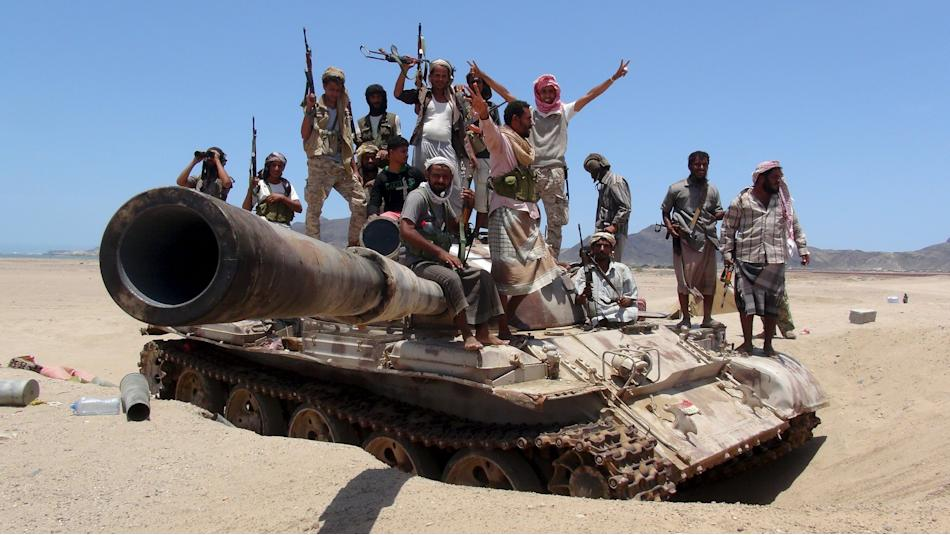 Anti-Houthi fighters of the Southern Popular Resistance stand on a tank in Yemen's southern port city of Aden