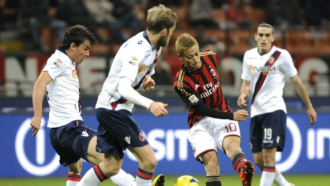AC Milan's Keisuke Honda kicks a ball near Bologna's Rene Khrin and Mikael Antonsson during their Italian Serie A soccer match against Bologna in Milan
