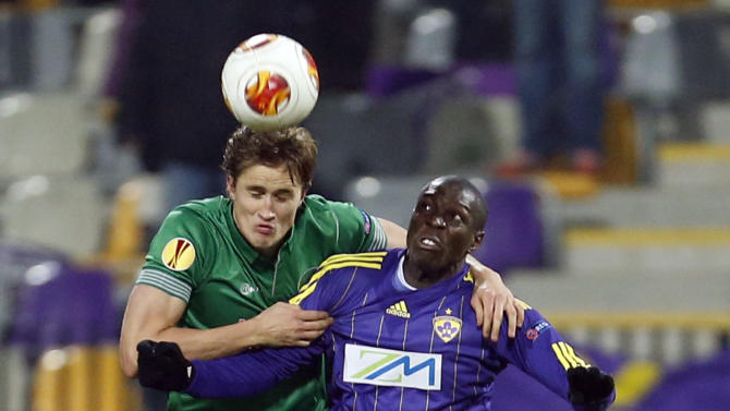 Wigan's Thomas Rogne, left, vies for the ball with Maribor's Jean Philippe Mendy during their group D Europa League soccer match, in Maribor, Slovenia, Thursday, Dec. 12, 2013