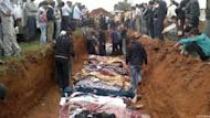 A picture released by the Local Coordination Committees in Syria (LCC) purportedly shows people standing around a mass grave in the town of Taftnaz on April 5, as bodies are laid out for burial in Idlib province. AFP cannot independently verify this image. Syria says it will not withdraw from protest hubs without written guarantees from the opposition groups