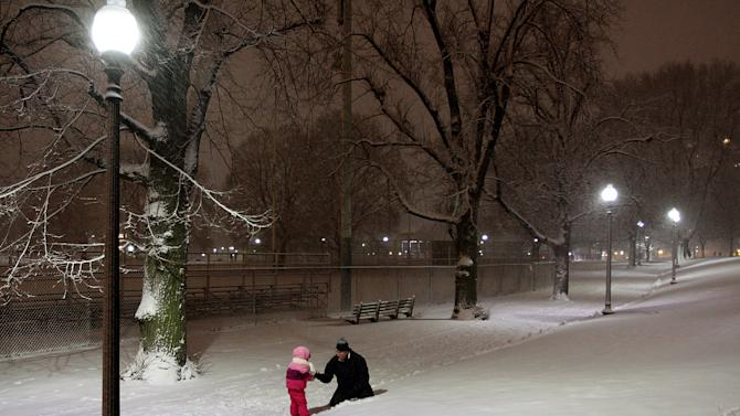A father plays with his son on Boston Common in Boston, during a snow storm Friday evening, Feb. 8, 2013. Snow began to fall as a massive blizzard headed for the American Northeas, sending residents scurrying to stock up on food and supplies ahead of a storm poised to dump up to 3 feet of snow from New York City to Boston and beyond. (AP Photo/Palm Beach Post, Mark Edelson)  MAGS OUT; TV OUT; NO SALES