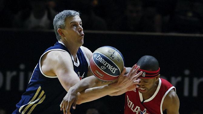 East's United States Secretary of Education Arne Duncan, left, battles West's Terrence Jenkins (13) for a loose ball in the first half as they participate in the NBA All-Star Celebrity basketball game in New Orleans, Friday, Feb. 14, 2014. East won 60-56