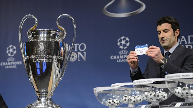 Former Portugal national  soccer player and Champions League Lisbon final ambassador Luis Figo shows a ticket with Spain's soccer team FC Barcelona during the draw of the round of 16 games of UEFA Champions League 2013/14 at the UEFA Headquarters in Nyon, Switzerland, Monday, Dec. 16, 2013