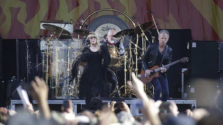 Stevie Nicks, left, Mick Fleetwood, center, and Lindsay Buckingham, are seen on stage as Fleetwood performs at the New Orleans Jazz and Heritage Festival in New Orleans, Saturday, May 4, 2013. (AP Photo/Gerald Herbert)