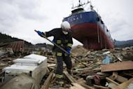 A Japanese firefighter looks for bodies next to a grounded fishing boat in Kesennuma, Miyagi prefecture, on March 21, 2011 after the March 11 tsunami and earthquake devastated northeastern Japan. Japan's government on Wednesday unveiled a worst case disaster scenario that warned a monster earthquake in the Pacific Ocean could kill over 320,000 people, dwarfing last year's quake-tsunami disaster