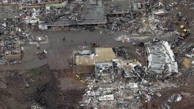 "FILE - A Tuesday, May 21, 2013 file photo, an aerial view shows Plaza Towers Elementary School, which was destroyed in Monday's tornado, in Moore, Okla. Unlike several others schools in the Oklahoma City area, Plaza Towers had no ""safe room"" in which students and teachers could huddle. The deaths of seven students at Plaza Towers highlights the patchwork of protection that exists at schools in tornado-prone parts of the central U.S.  (AP Photo/Tony Gutierrez, File)"