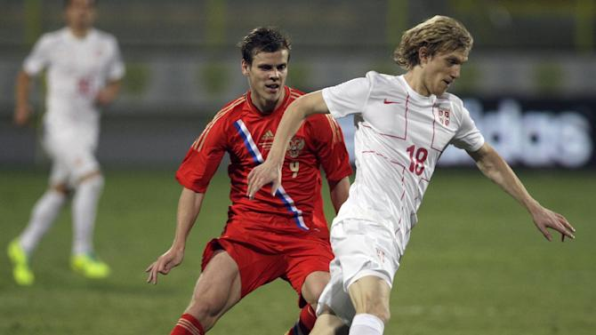 Serbia's Dusan Basta, right, runs with the ball with Russia's Alexander Kokorin follows him during a friendly match Dubai, United Arab Emirates, Friday Nov. 15, 2013