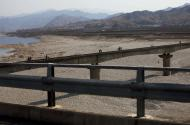In this April 19, 2011 photo, people walk and use bicycles to cross a railroad bridge over a riverbed north of Pyongyang, North Korea. (AP Photo/David Guttenfelder)