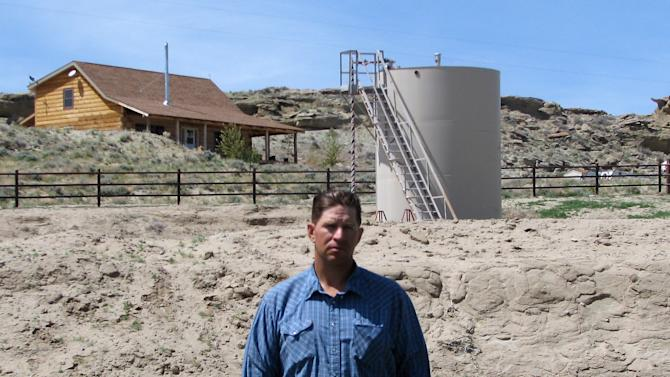 "ADVANCE FOR FRIDAY AMS MAY 4 - FILE - A May 22, 2009 picture shows John Fenton, a farmer who lives near Pavillion in central Wyoming, near a tank used in natural gas extraction, in background. Fenton and some of his neighbors blame hydraulic fracturing, or ""fracking,"" for fouling their well water. The U.S. Environmental Protection Agency drew skepticism and mistrust from Wyoming regulators after it privately briefed them more than a month in advance about its first-ever public announcement that hydraulic fracturing, a controversial but favored method for releasing difficult pockets of oil and gas, might have caused groundwater pollution. (AP Photo/Bob Moen, File)"