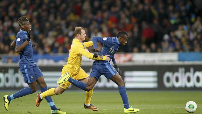 Ukraine's Roman Zozulya fights for the ball with France's Blaise Matuidi and Paul Pogba during their 2014 World Cup qualifying first leg playoff soccer match at the Olympic stadium in Kiev
