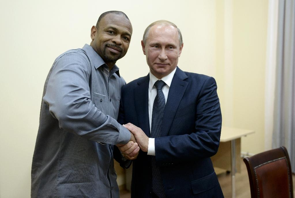 Russian President Vladimir Putin (right) shakes hands with US boxer Roy Jones Jr. during a meeting in Sevastopol, on August 19, 2015