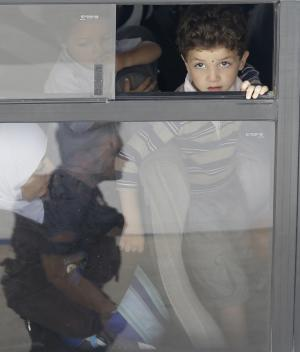 A boy looks out from the window of a bus as he wait to board a ship heading to Sicily, in Lampedusa, Italy, Friday, Oct. 4, 2013. A ship carrying African migrants toward Italy caught fire and capsized off the Sicilian island of Lampedusa Thursday, spilling hundreds of passengers into the sea. Over one hundred bodies were recovered but over 200 people are unaccounted-for. It was one of the deadliest accidents in recent times during the notoriously perilous crossing from Africa for migrants seeking a new life in the European Union. (AP Photo/Luca Bruno)