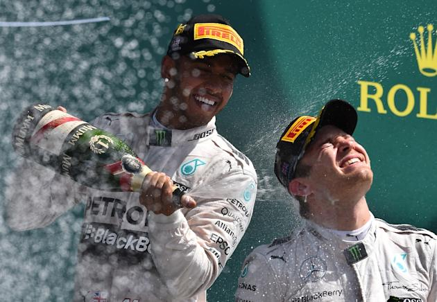 Mercedes AMG Petronas F1 Team's British driver Lewis Hamilton sprays champagne on second placed teammate Mercedes AMG Petronas F1 Team's German driver Nico Rosberg (R) on the podium after winn