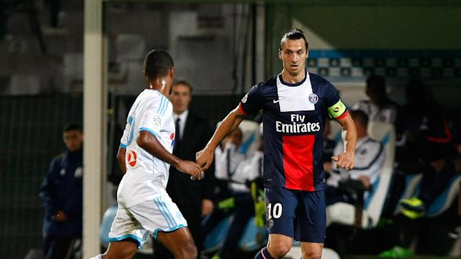 Paris Saint Germain's Swedish forward Zlatan Ibrahimovic, right, challenges for the ball with Marseille's Togolese midfielder Jacques-Alaixys Romao, during their League One soccer match, at the Velodrome Stadium, in Marseille, southern France, Sunday, Oct. 6, 2013